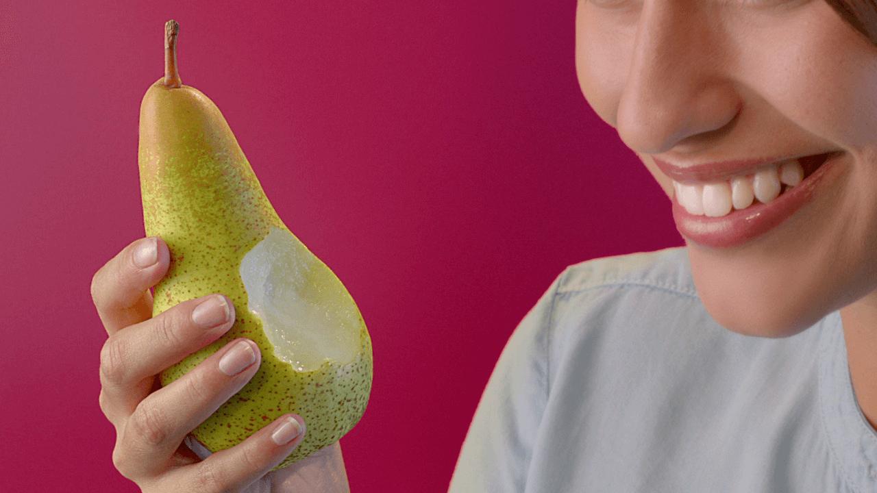 Donna con in mano una pera morsicata