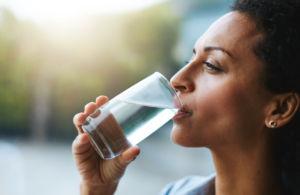 Donna che beve acqua in primo piano