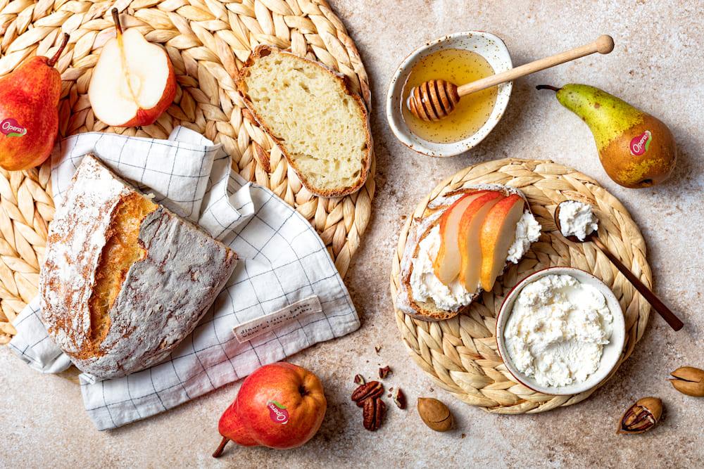 Tavola imbandita con formaggio, pere e pane casareccio