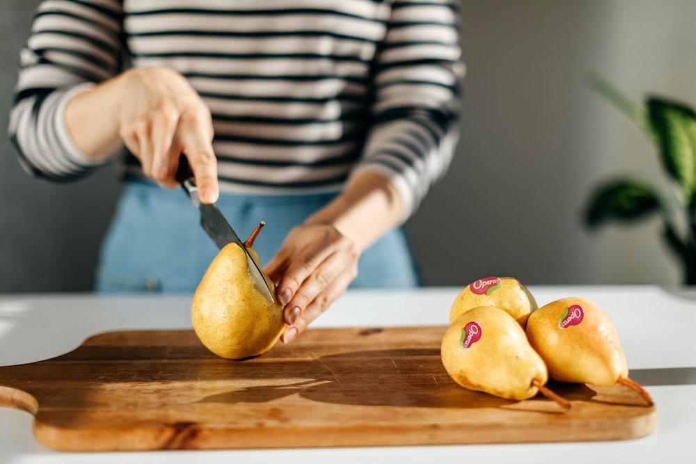 Donna che taglia una pera su un vassoio in legno